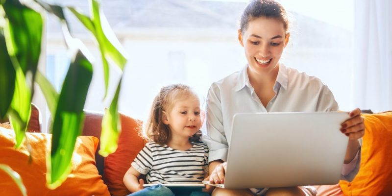Happy loving family. Young mother and her daughter girl play in room. Funny mom and lovely child are having fun with laptop.